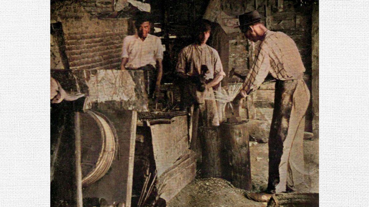 Manuel Cagancho –al fondo, con camisa blanca– e hijos. Reportaje sobre las fraguas de Triana, 1912.